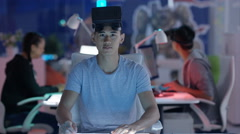 4K Computer game designer looks directly into camera before putting on VR viewer Stock Footage