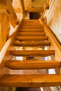 Wooden stairs leading upstairs in handcrafted red cedar log home, Quebec, Canada Stock Photos