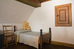 Old wooden chair and single bed in a bedroom in old (1785) fieldstone cottage Stock Photos