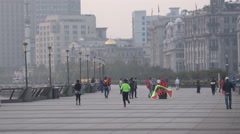 Locals visit the Bund in the early morning, flying kites, running, Shanghai Stock Footage