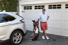 Portrait of senior male golfer standing next to garage door with golf bag Stock Photos