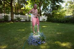 Senior man in garden watering flower hanging basket Stock Photos