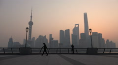 Beautiful Shanghai skyline at sunrise, silhouettes of people doing morning walk Stock Footage