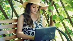 Pretty girl looking absorbed while typing on laptop in the arbor Stock Footage