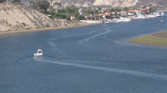 Long  shot of Motorboat being towed and two paddle boarders along a cliff and Stock Footage
