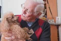 Senior man carrying pet dog at home Stock Photos