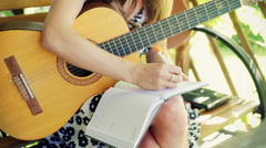Girl writing music in her notebook and trying to play on guitar Stock Footage