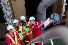 Engineers in brainstorming session on oil rig Stock Photos