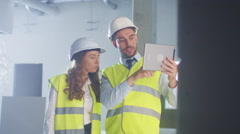 Two Engineers in Hard Hat are using Tablet Computer of Augmented Reality. Stock Footage
