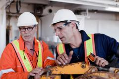 Engineers in discussion on oil rig Stock Photos