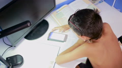 Teenage boy doing homework using a cell phone. natural video Stock Footage