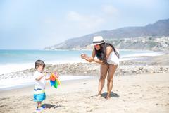 Mother photographing baby son on beach, Malibu, California, USA Stock Photos