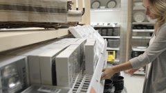 Young woman chooses dishes in the supermarket Stock Footage