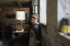 Portrait of teenage boy wearing tinted eyeglasses leaning against shed wall Stock Photos