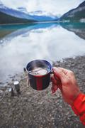 Cropped view of mans hand holding cup of tea by river, Banff, Alberta, Canada Stock Photos