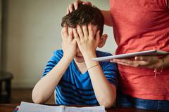 Mother comforting upset son doing homework Stock Photos