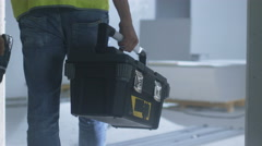 Construction Worker Walking inside Building Under Construction and Carrying Tool Stock Footage