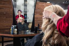 Stylist attending to customer in hair salon Stock Photos