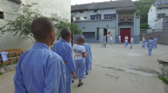 Young kung fu students watch their coach explain a training exercise in Shaolin Stock Footage