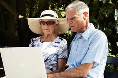 Senior couple sitting using laptop in park Stock Photos