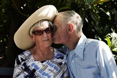 Romantic senior man kissing wife on cheek in park Stock Photos