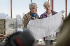 Female carpenters discussing blueprint design in furniture making workshop Stock Photos