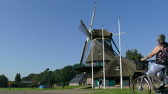Women passing by on bicycle at windmill in Dutch Landscape Stock Footage