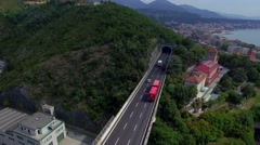 Road bridge in mountains with cars and lorries moving and seaside town 4k aerial Stock Footage