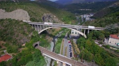 Lorry trucks move on road bridge in rock mountain up railway bridge 4k aerial Stock Footage