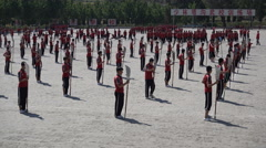 Chinese martial arts students train with swords and weapons at kung fu school Stock Footage