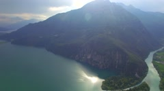 Fly over rock Alps mountain and river flow to Como Lake sun reflection 4k aerial Stock Footage