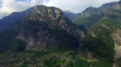 Rocky mountain and town in valley at foot aerial close up Lake Como in Italy Stock Footage