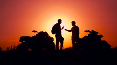 Silhouettes of men and ATVs at sunset. Men shake hands Stock Footage