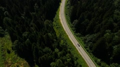 Aerial Black car moving on the road in the pine forest mountains Stock Footage