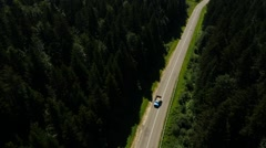 Aerial old truck moves in the pine forest near the village in the mountains Stock Footage