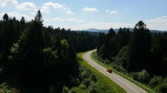 Aerial Orange car moving on the road in the pine forest mountains Stock Footage