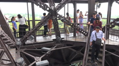 Chinese visitors walk down a scale model of the Eiffel Tower in France Stock Footage