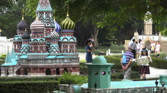 Chinese tourists walk past a scale model of the Kremlin in Moscow Stock Footage
