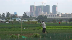 China urbanization, expanding city, farmer at work in fields rural village Stock Footage
