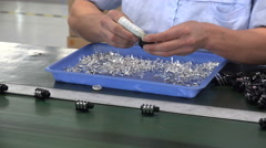 Female factory worker assembles electronic parts on the conveyor belt China Stock Footage