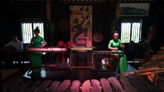 Two young asian women dressed long green dress are playing musical instruments Stock Footage