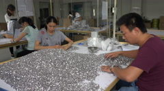 Checking, sorting, and packing buttons in a factory in Dongguan, China Stock Footage