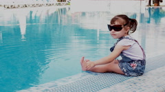 Little girl sitting next to the blue pool Stock Footage