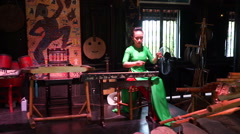 Young asian women dressed long green dress is playing musical instrument Dan Bau Stock Footage
