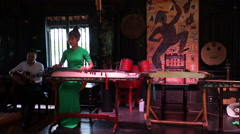 Young asian women dressed long green dress is playing musical instrument Koto in Stock Footage