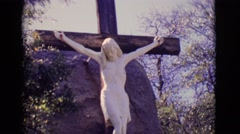 1965: jesus nailed to a large wooden cross with a large boulder  Stock Footage