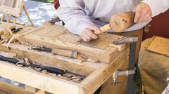 Carpenter, craftsman carving wood in a medieval fair, carpentry tools Stock Photos