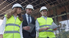 Team of Two Engineers and Businessman in Hard Hat Walking, Talking. Stock Footage