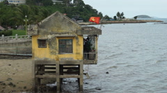 Small ragged lodge with Vietnamese flag fluttering on wind near the river bank Stock Footage