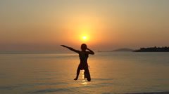 Child little girl is jumping into the sea from a pier at sunset. Slow motion Stock Footage